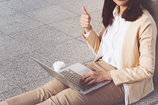 Businesswoman in high heels sitting on floor with computer in her lap