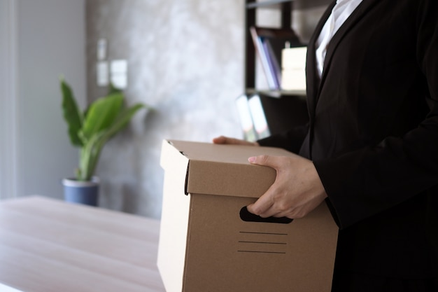 Businesswoman hold boxes for personal belongings and resignation letters.