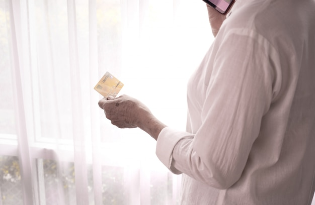 Businesswoman hold credit card and using phone on white curtain