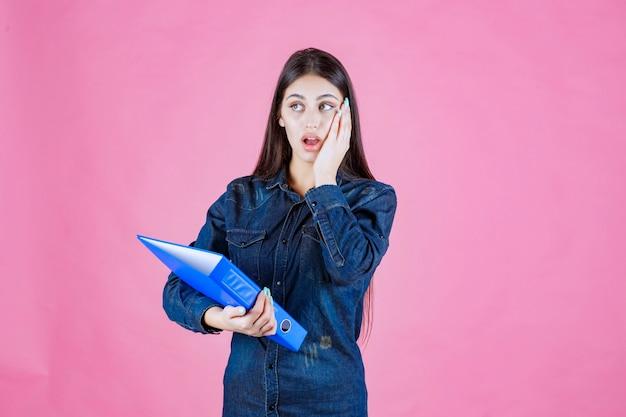 Деловая женщина держит синий контрольный список и выглядит смущенным