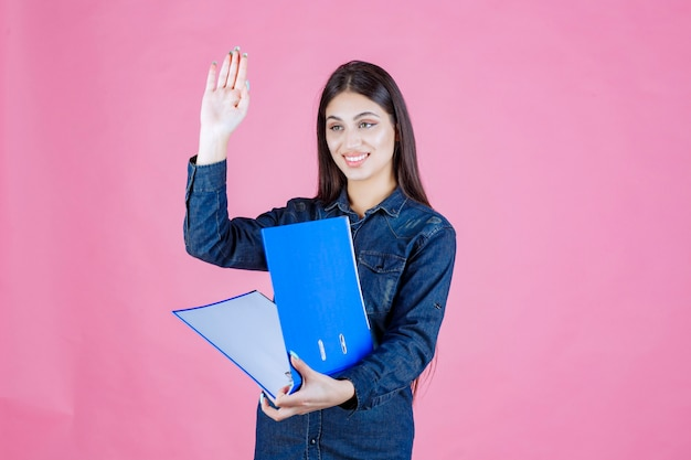 青いフォルダーを保持し、手を振って誰かに挨拶する実業家