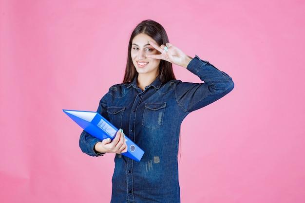 Деловая женщина держит синюю папку и отправляет знак мира