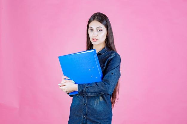 Деловая женщина, держащая синюю папку с уверенностью в себе