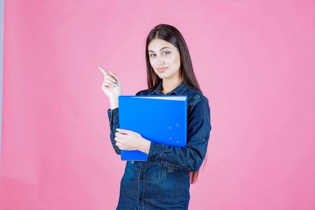 Деловая женщина держит синюю папку с отчетом и указывает вверх