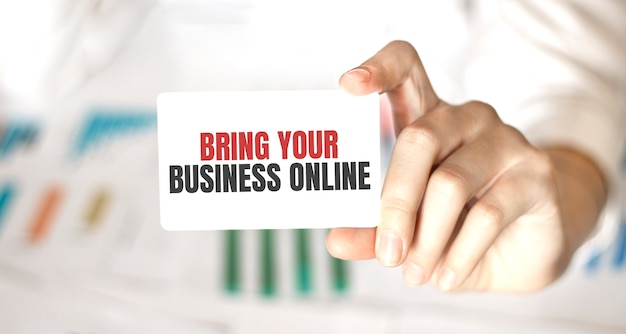 テキスト付きのカードを持っている実業家あなたのビジネスをオンラインにする