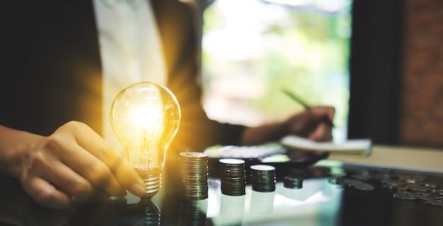 計算し、エネルギーとお金の概念を節約するためにテーブルの上のコインスタックで書き込みながら電球を保持している実業家