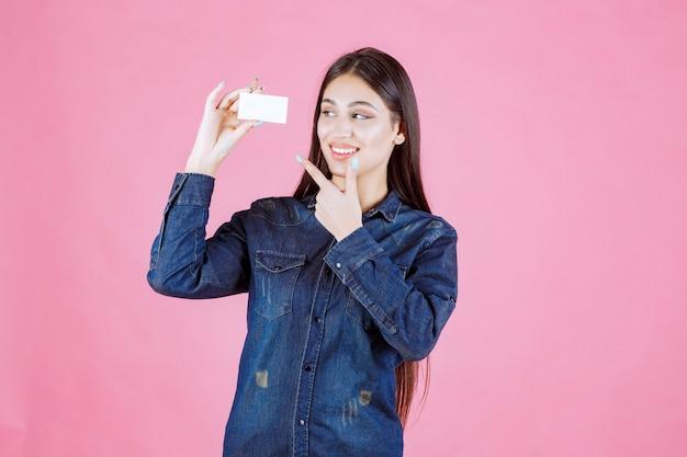 Деловая женщина, держащая и указывая на ее визитную карточку