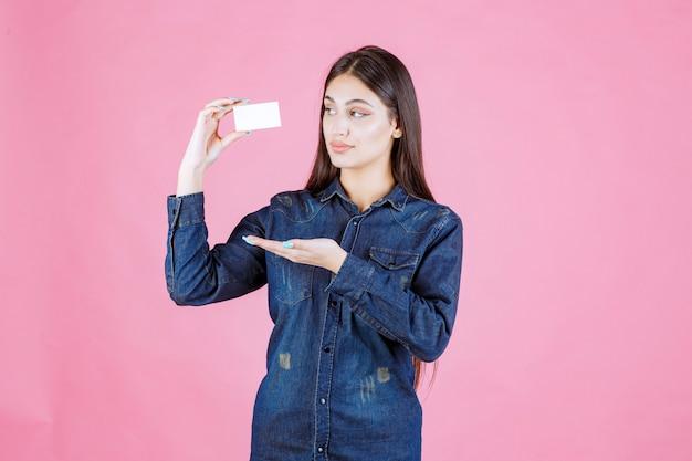 Деловая женщина держит и представляет свою новую визитную карточку