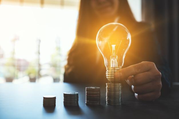 エネルギーとお金の概念を節約するためにテーブルの上のコインスタックに電球を保持して置く実業家