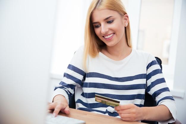 Деловая женщина держит банковскую карту и печатает на клавиатуре