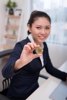 Деловая женщина, держащая биткойн в офисе, цифровые деньги и концепцию биткойнов.