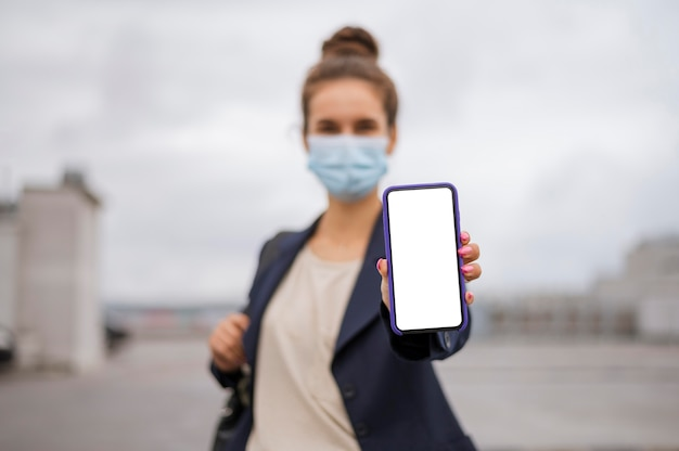 Businesswoman holding a blank smartphone while wearing a medical mask