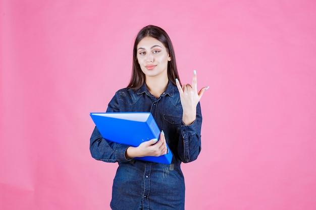 Donna di affari che tiene una cartella di progetto blu e che mostra il segno freddo della mano