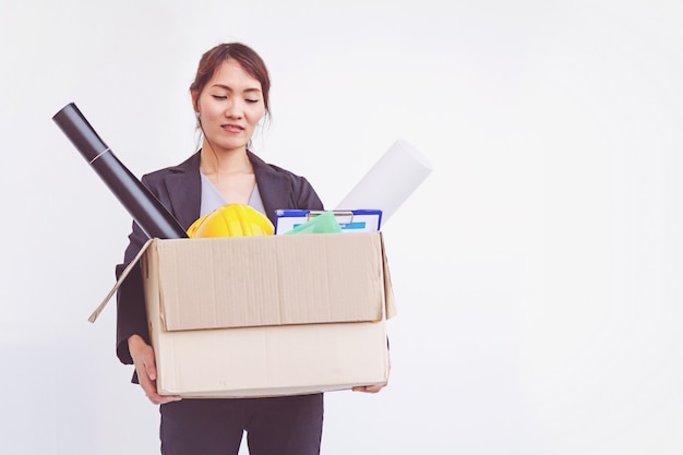 Businesswoman holding box leaving office after quitting job