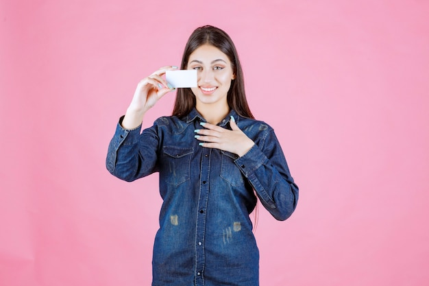 Businesswoman holding a business card and pointing at herself