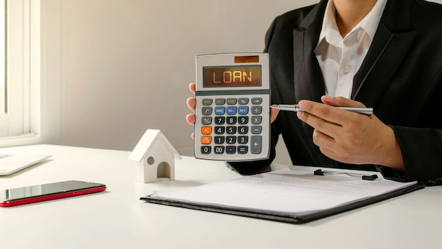 Businesswoman holding a calculator and pointing a pen to the loan text on the sme loan concept calculator