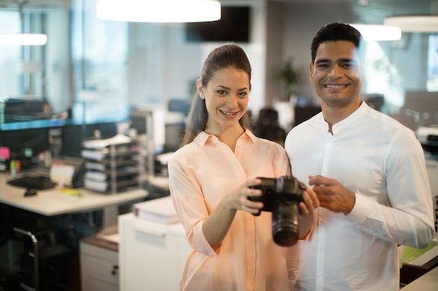 Businesswoman holding camera with colleague Premium Photo