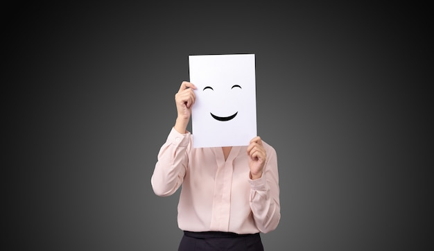 Businesswoman holding a card with drawing facial expressions illustrations emotion feelings face on white paper