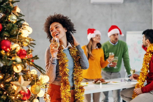 Businesswoman holding champagne on christmas eve in her firm. in background are her colleagues.