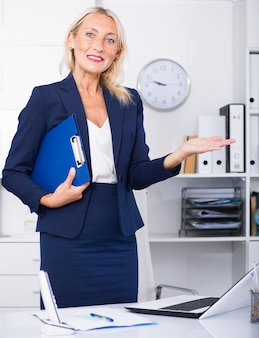 Businesswoman holding clipboard welcoming to office
