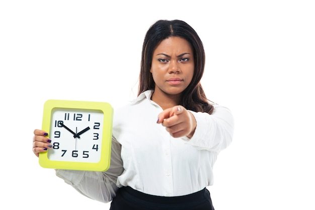 Businesswoman holding clock and pointing at camera