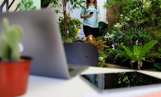 Деловая женщина, держащая чашку кофе и смартфон, идет из домашней комнаты к рабочему столу в угловом небольшом саду с ноутбуком и планшетным компьютером. понятие о новых нормальных людях и работе дома.