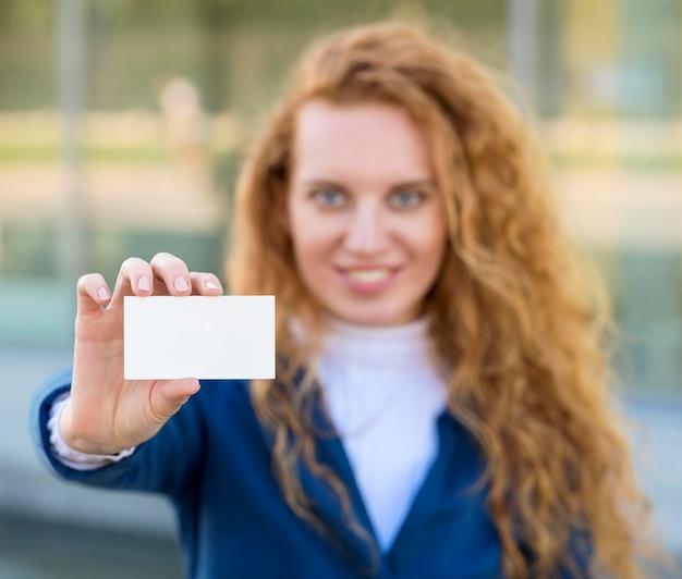 Donna di affari che tiene un biglietto da visita dello spazio della copia