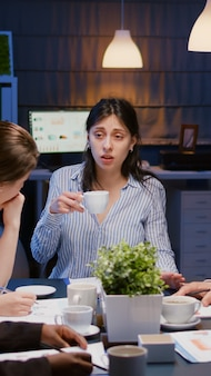 Businesswoman holding cup of coffee while discussing with multiethnic teamwork