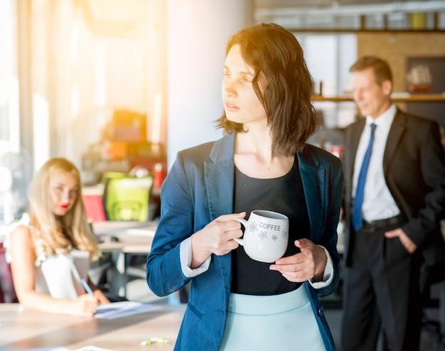 Donna di affari che tiene tazza di caffè