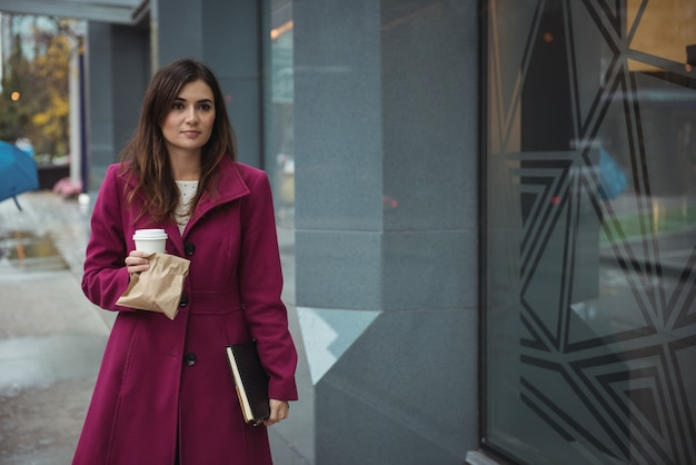 Businesswoman holding disposable coffee cup, parcel and diary