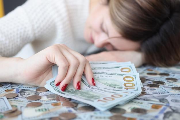 Деловая женщина держит доллары в руке и спит на деньгах. накопление денежной концепции
