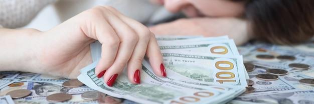 Деловая женщина, держащая доллары в руке и спящая на деньгах, накопление денежной концепции