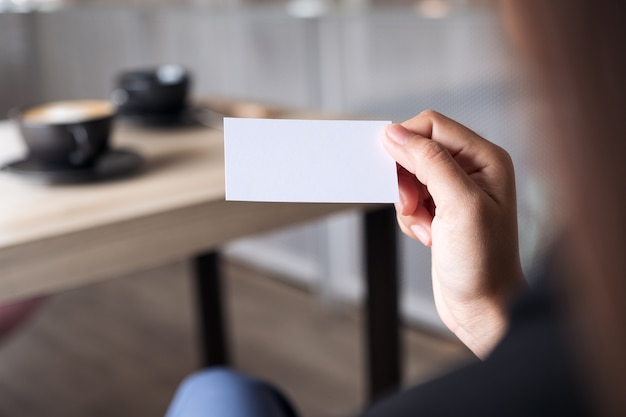 Businesswoman holding an empty business card while sitting in office