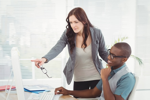 Businesswoman holding eyeglasses while looking at computer