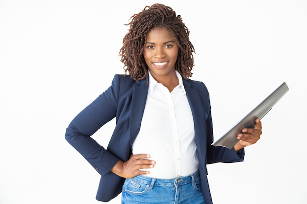 Businesswoman holding folder and smiling at camera