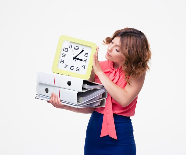 Businesswoman holding folders and looking on clock