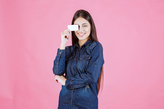 Businesswoman holding her business card to her eye