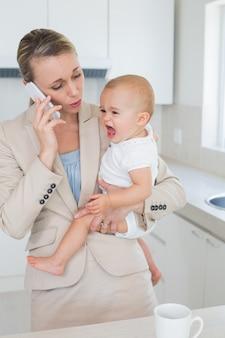 電話で話す彼女の泣いている赤ちゃんを保持するビジネスマン
