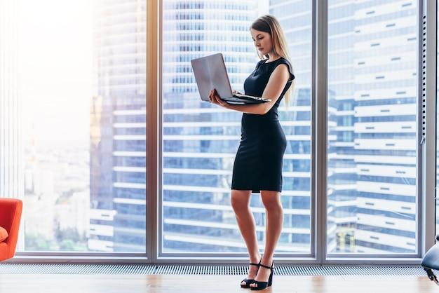 Деловая женщина, держащая ноутбук, стоя в современном офисе против окна с видом на город.