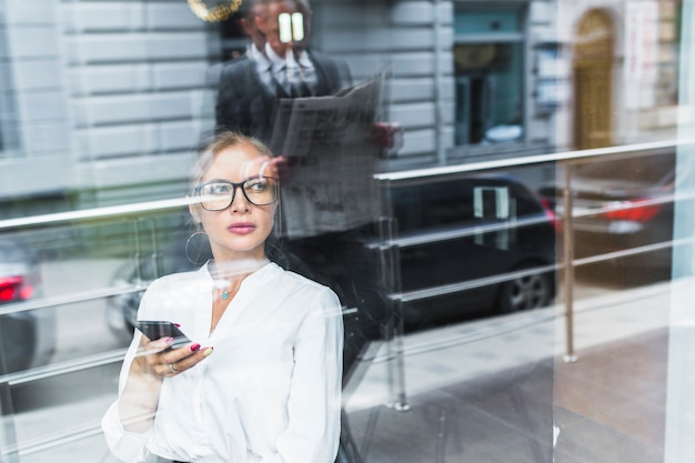 Businesswoman holding mobile phone with reflection of man reading newspaper