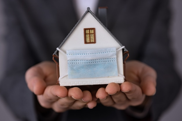 Businesswoman holding model house wearing protective mask in hands. support business during the coronavirus pandemic concept.