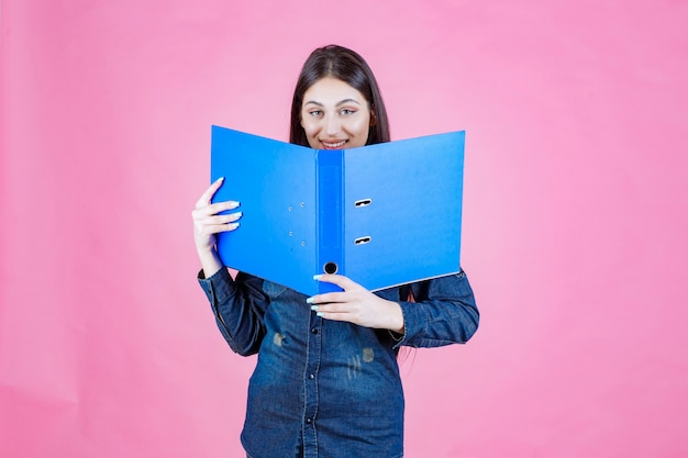 Businesswoman holding an open project folder and hiding her face behind it