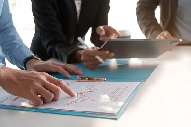 펜을 들고 그래프 용지를 들고 사업가가 내년에 설정된 목표를 달성하기 위해 판매 계획을 세우기 위해 회의를하고 있습니다.