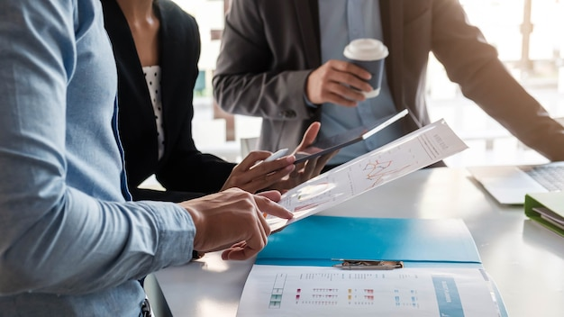 펜을 들고 그래프 용지를 들고있는 사업가가 내년에 설정된 목표를 달성하기 위해 판매 계획을 세우기 위해 회의를하고 있습니다.