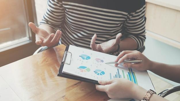 ペンと方眼紙を持っている実業家は、来年に設定された目標を達成するために販売を計画するために会合しています。
