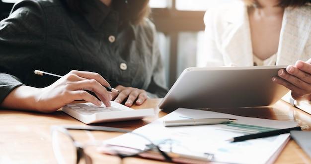 Деловая женщина с ручками и миллиметровой бумагой встречается, чтобы запланировать продажи для достижения целей, поставленных в следующем годуx