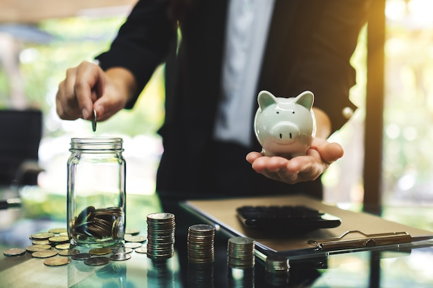Businesswoman holding a piggy bank while putting coin into a glass jar for saving energy and money concept