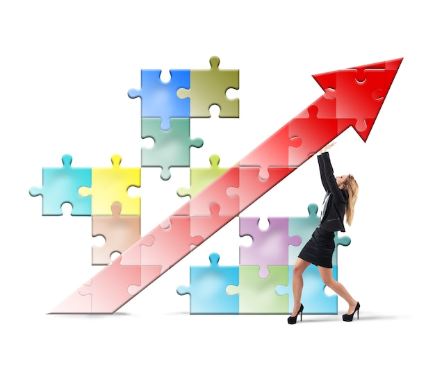 Businesswoman holding a puzzle with arrow pointing up