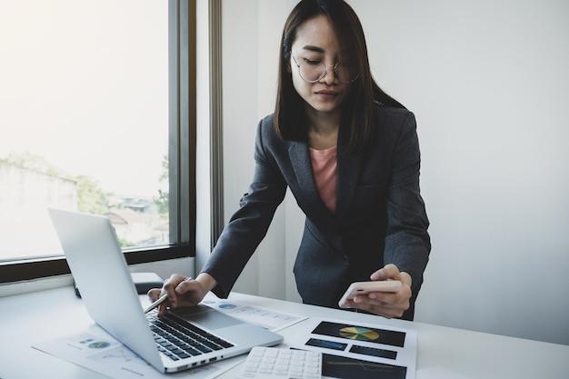 Деловая женщина, держащая анализ смартфона график с калькулятором и ноутбуком в офисе