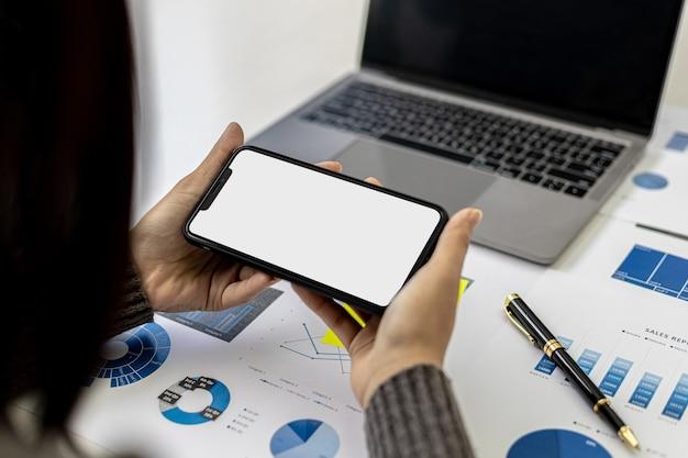 문서와 노트북이 놓인 책상 위에 스마트폰을 들고 있는 사업가, 그녀는 휴대전화의 데이터, 광고 그래픽을 위한 휴대전화 빈 화면을 보고 있습니다. 기술 사용의 개념